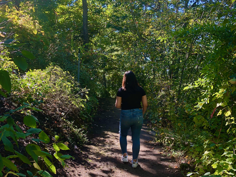 A students walks in the UC Botanical Garden.